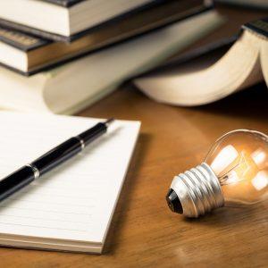 A blank notebook next to an illuminated lightbulb.