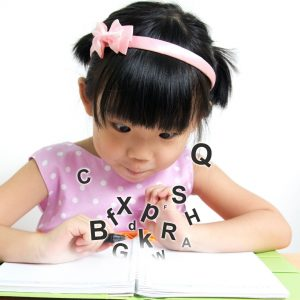Little girl watching words fly out of a book